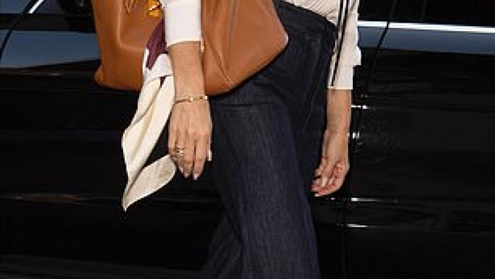 Cô diện áo sơ mi lụa trắng, quần jeans ống rộng chấm gót chân sành điệu.