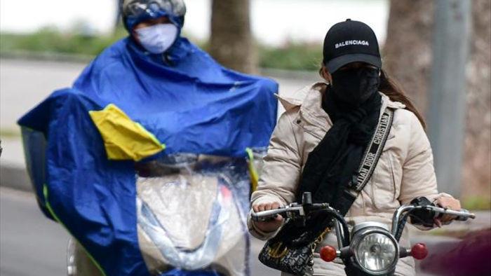 Ảnh: Trời tạnh ráo, người Hà Nội vẫn mặc áo mưa tránh gió rét 12 độ C - 2
