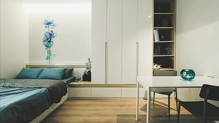 Tủ quần áo được bố trí ở phía đầu giường, cao sát trần để tận dụng không gian chứa đồ. Màu sắc nội thất sử dụng màu trắng điểm xuyết sắc xanh cho cảm giác rộng rãi và mát mẻ. Thiết kế loại bỏ những trang trí không cần thiết có thể gây rối mắt hay chật chội.
