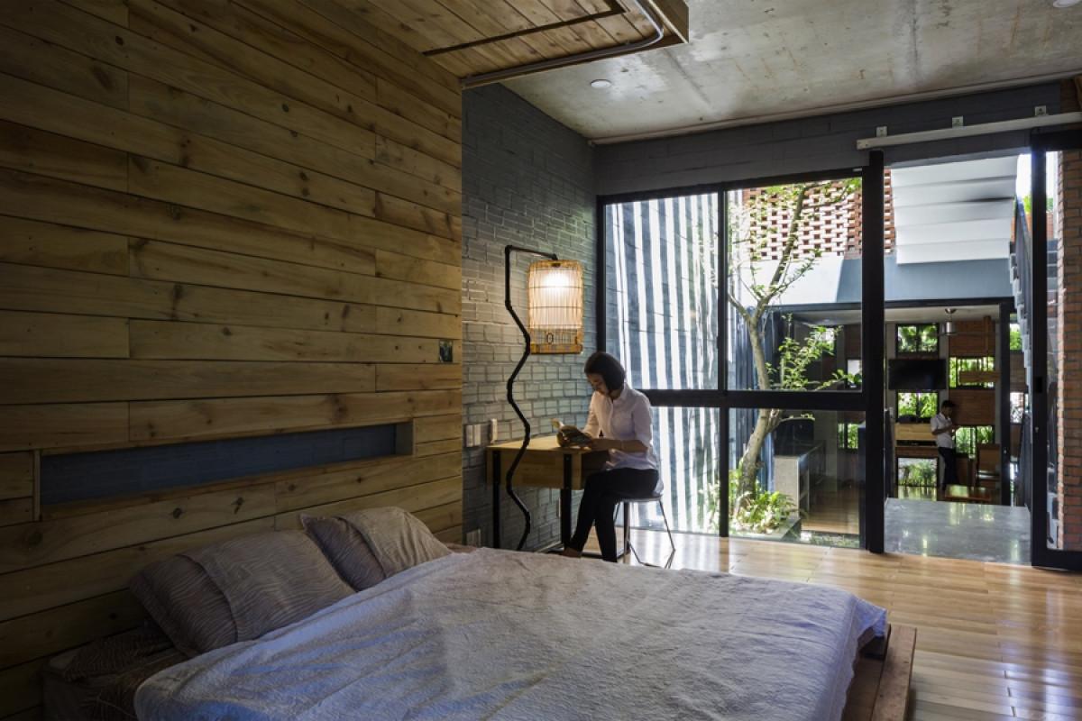 Phòng ngủ ở tầng 2 mộc mạc, giản dị. Vách kính lớn mở ra khoảng giếng trời và cầu thang làm không gian càng thêm rộng.