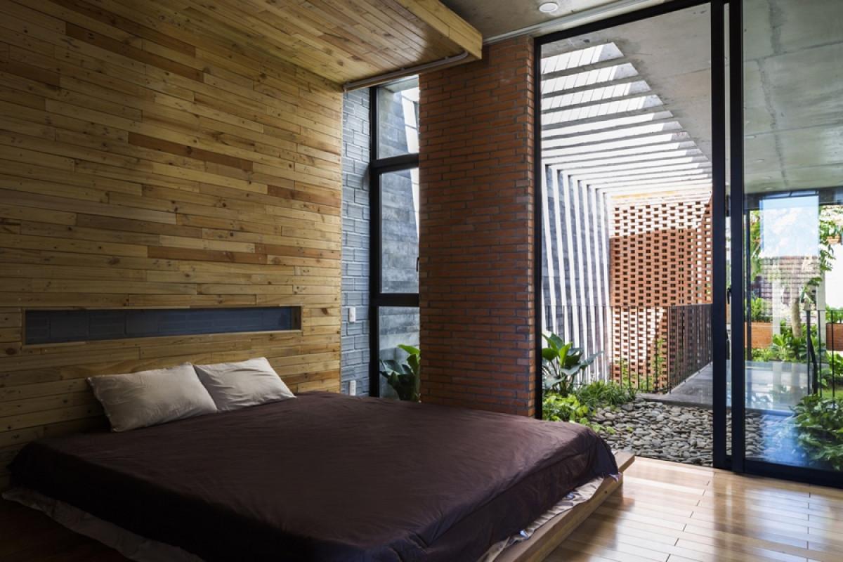 Phòng ngủ ở tầng 3 với khoảng hiên sỏi và cây xanh phía trước cửa.