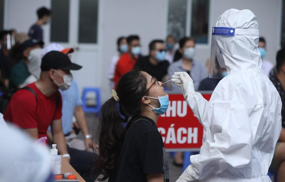 Nhân viên y tế quận Hai Bà Trưng lấy mẫu xét nghiệm COVID-19 cho các trường hợp trở về từ Thành phố Hồ Chí Minh ngày 10/7/2021. (Ảnh: Minh Quyết/TTXVN)