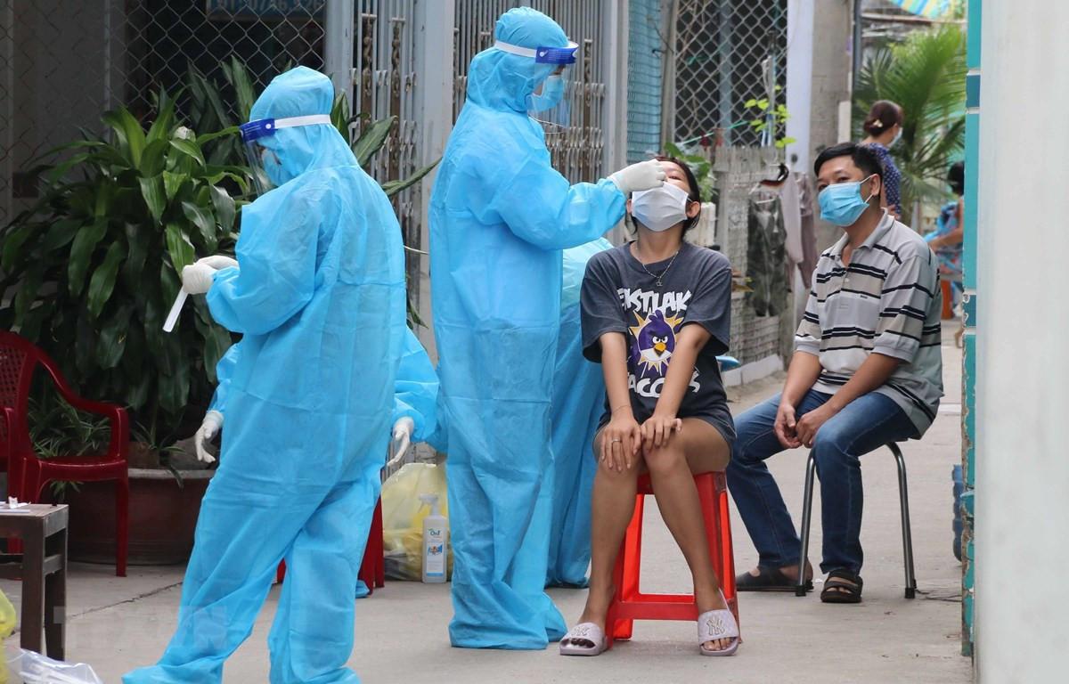 Lấy mẫu xét nghiệm SARS-CoV-2 tại Trà Vinh. (Ảnh: Thanh Hòa/TTXVN)