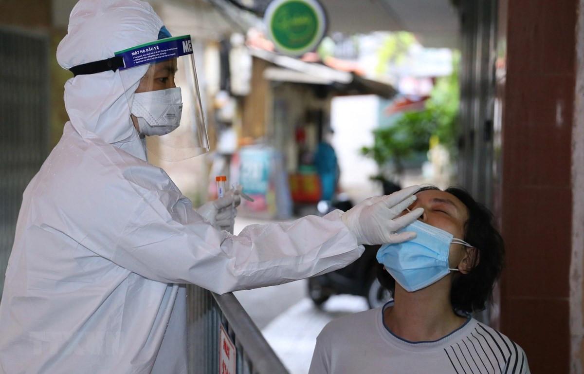 Lực lượng y tế lấy mẫu xét nghiệm SARS-CoV-2 cho những người có nguy cơ cao. (Ảnh: Hoàng Hiếu/TTXVN)