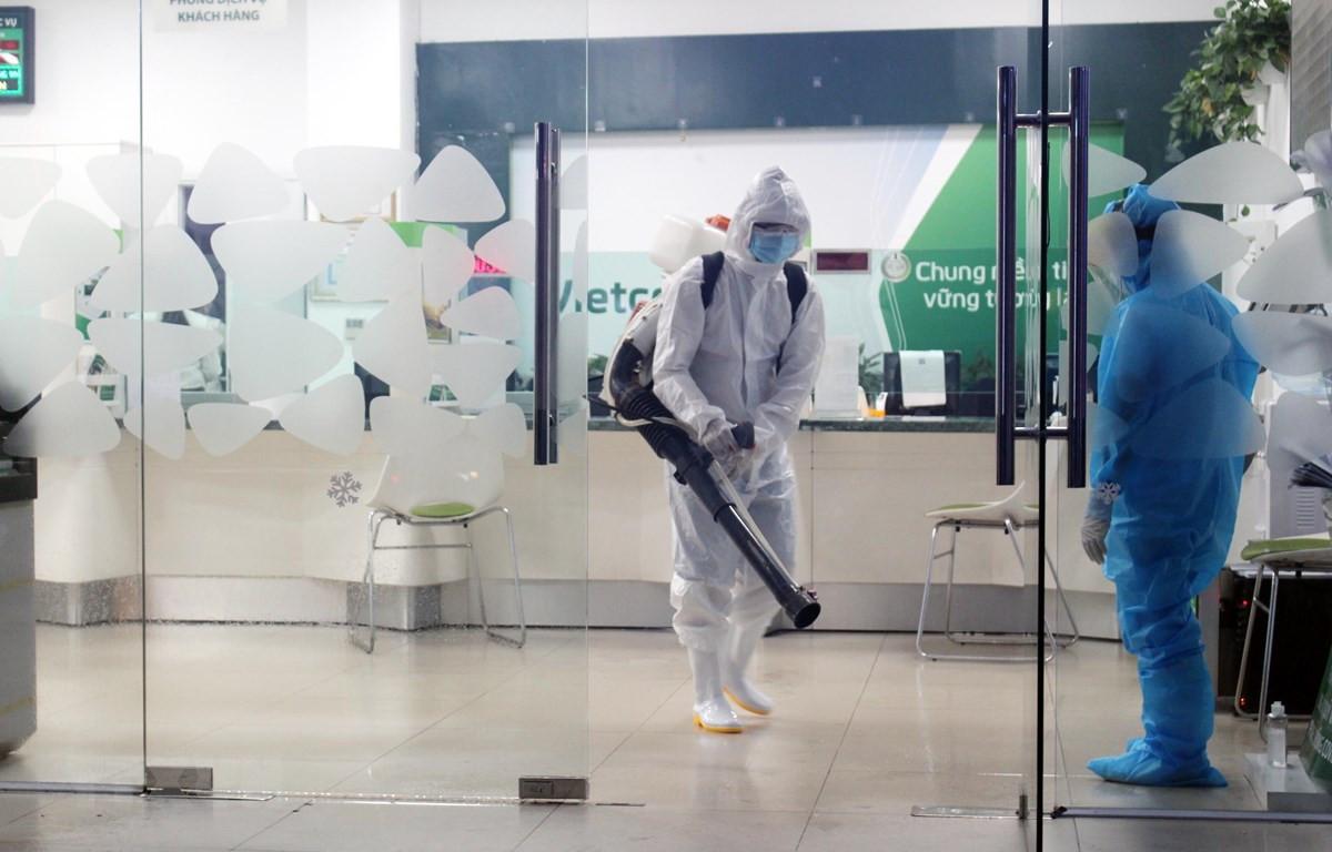 Lực lượng chức năng phun thuốc khử khuẩn trụ sở Ngân hàng Vietcombank, thành phố Thái Nguyên nơi liên quan đến một bệnh nhân COVID-19. (Ảnh: Trần Trang- TTXVN)