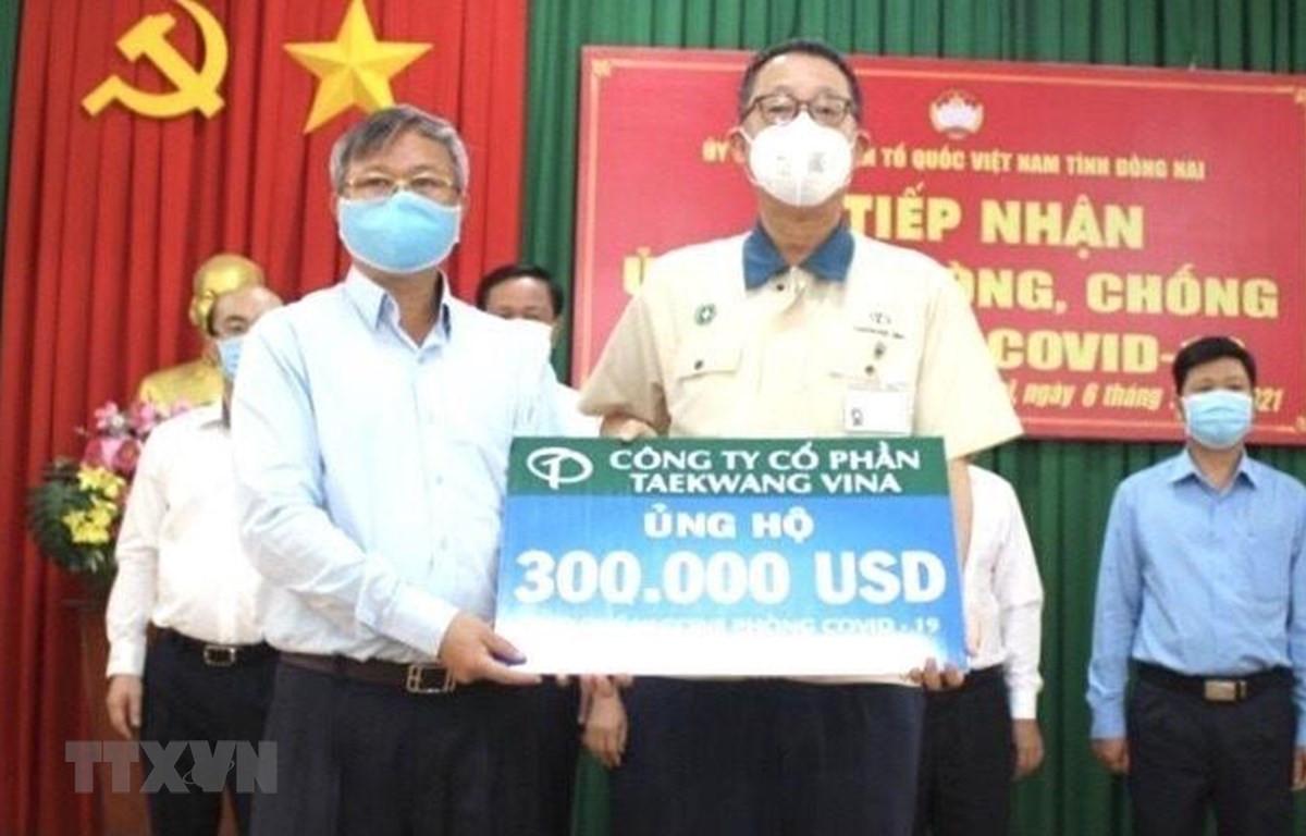 Chủ tịch UBND tỉnh Đồng Nai Cao Tiến Dũng (trái) tiếp nhận 300.000 USD từ Đại diện Công ty cổ phần Taekwang Vina ủng hộ Quỹ vaccine phòng, chống dịch COVID-19. (Ảnh: TTXVN phát)