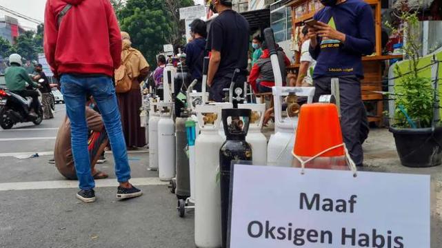 Biển báo có nội dung 'xin lỗi, hết ôxy' được nhìn thấy khi mọi người xếp hàng bên ngoài một cửa hàng nạp ôxy để đổ đầy bình cho các thành viên trong gia đình bị bệnh ở Jakarta. Hình: AFP Nguồn: AFP