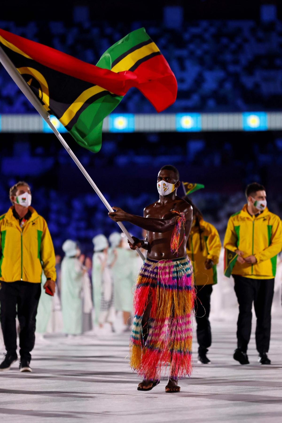 VĐV chèo thuyền Rio Rii cũng cởi trần, bôi dầu, mặc trang phục truyền thống Vanuatu diễu hành trong lễ khai mạc Olympic Tokyo.