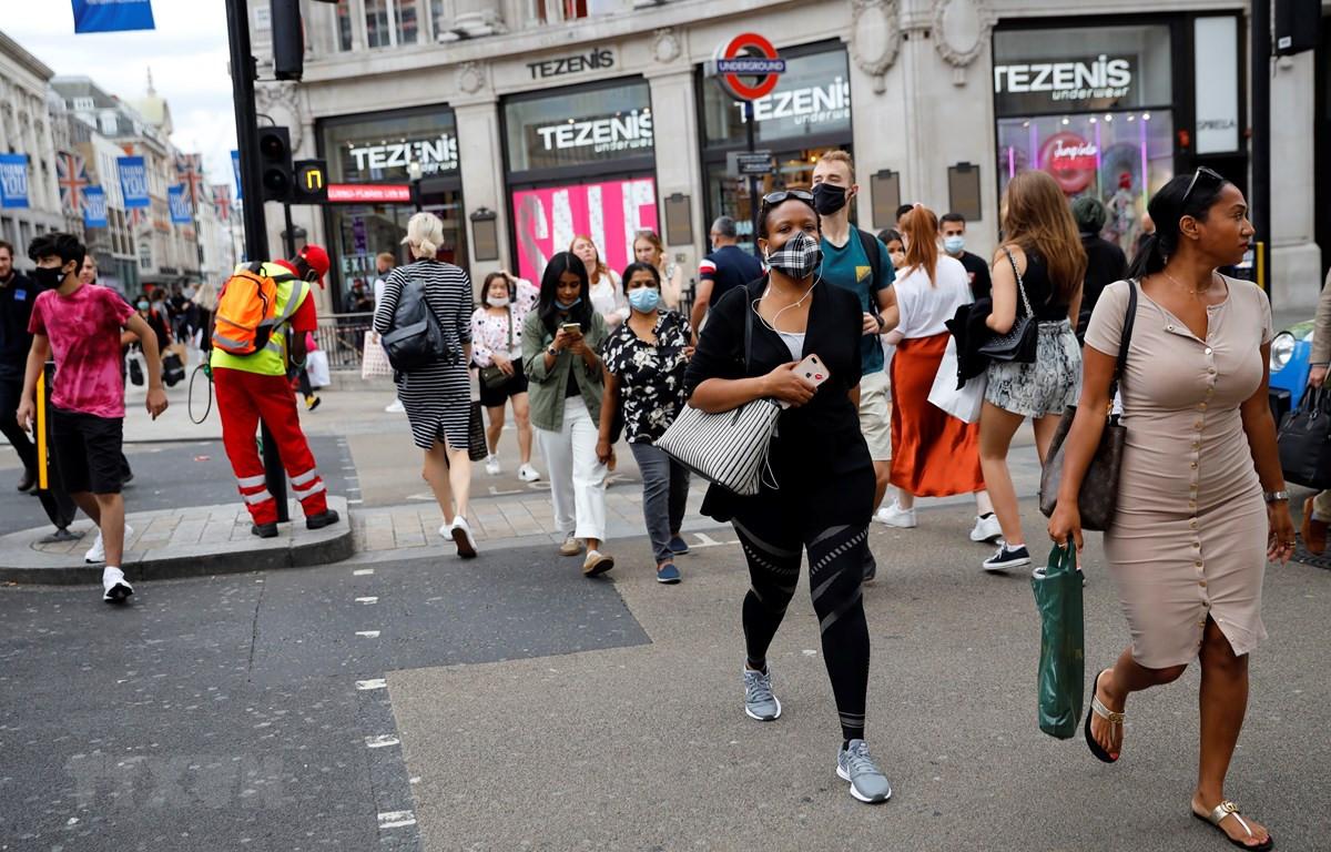 Người dân đeo khẩu trang phòng lây nhiễm COVID-19 khi di chuyển trên đường phố tại London, Anh ngày 24/7/2020. (Ảnh: AFP/TTXVN)
