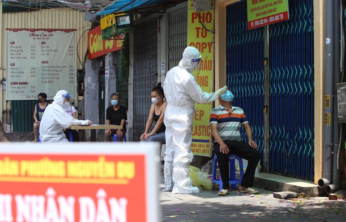 Lực lượng y tế quận Hai Bà Trưng lấy mẫu xét nghiệm cho người dân phố Tô Hiến Thành. (Ảnh: Hoàng Hiếu/TTXVN)