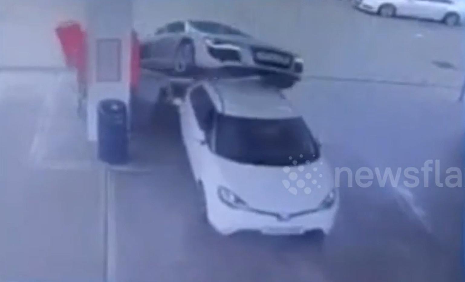 Chiếc Audi bất ngờ vọt tới chồm lên chiếc ô tô màu trắng đang dừng đổ xăng