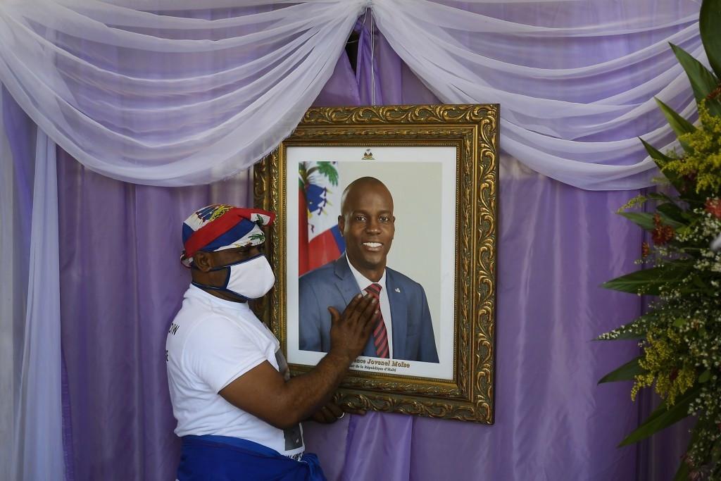 Người đàn ông chạm vào chân dung của cố Tổng thống Haiti Jovenel Moise bên ngoài một nhà thờ lớn ở Cap-Haitien, Haiti, nơi tổ chức lễ tưởng niệm, ngày 22/7. Ông Moise đã bị ám sát hồi đầu tháng tại nhà riêng bởi một nhóm sát thủ. (Nguồn: AP)