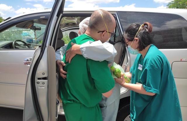 Một bệnh nhân tuổi cao được các bác sĩ bế lên xe để trở về với gia đình