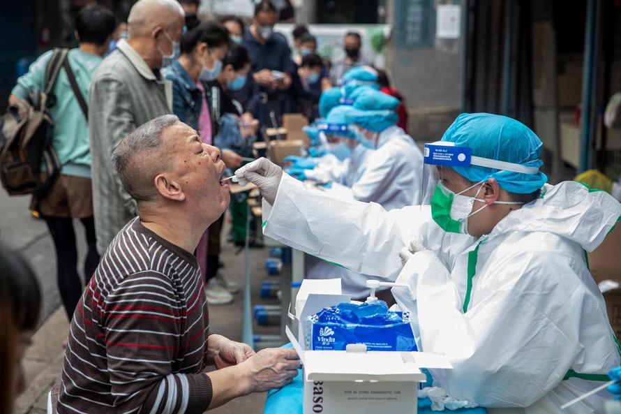 Nhân viên y tế lấy mẫu xét nghiệm COVID-19 cho người dân tại Vũ Hán. Ảnh: Xinhua
