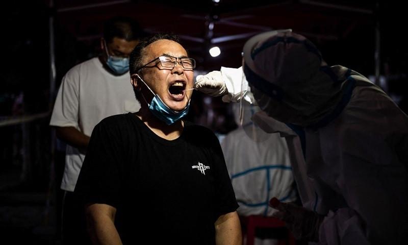 Người dân thành phố Vũ Hán, tỉnh Hồ Bắc được xét nghiệm Covid-19 trong đêm 3/8. Ảnh: AFP.