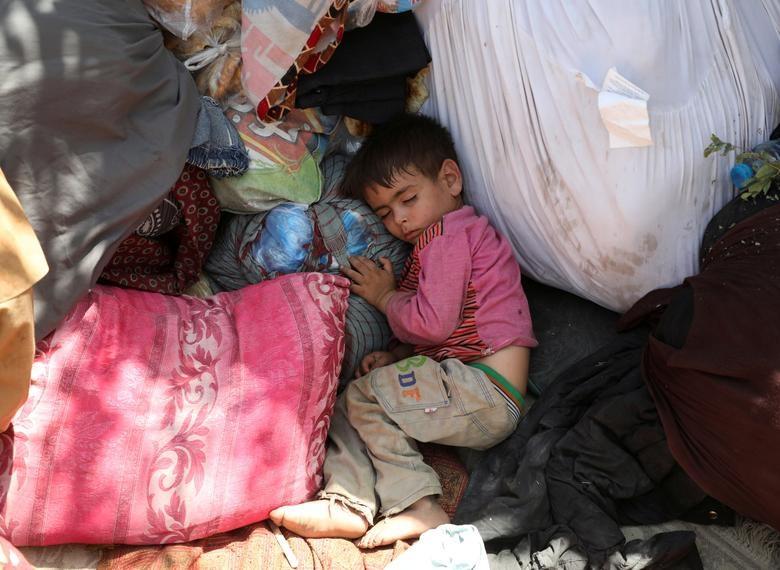 Một đứa trẻ di tản từ các tỉnh phía bắc, trốn khỏi nhà do giao tranh giữa Taliban và lực lượng an ninh Afghanistan, ngủ trong một công viên công cộng mà chúng sử dụng làm nơi trú ẩn ở Kabul, Afghanistan, ngày 10 tháng 8. REUTERS / Stringer