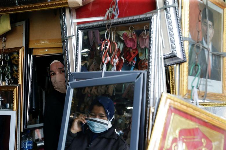 Người phụ nữ đeo khẩu trang khi bán hàng trong bối cảnh dịch Covid-19 đang bùng phát dữ dội ở Jakarta, Indonesia, ngày 18/8. (Nguồn: Reuters)