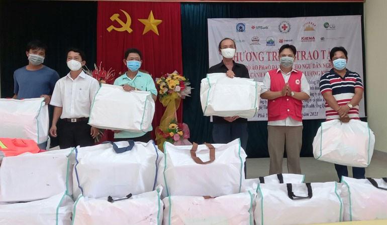 Phó Chủ tịch Hội Chữ thập đỏ tỉnh Nguyễn Hữu Sửu (thứ 2 từ phải sang) và đại diện lãnh đạo phường Phú Đông tặng bộ áo phao cứu sinh cho gia đình các ngư dân địa phương. Ảnh: NGỌC DUNG
