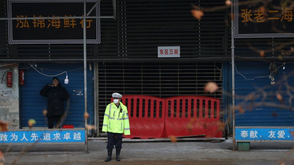 Một sĩ quan cảnh sát đứng trước chợ thủy sản có liên quan đến đợt bùng phát virus corona ở Vũ Hán, Trung Quốc vào tháng 1 năm 2020. © Reuters