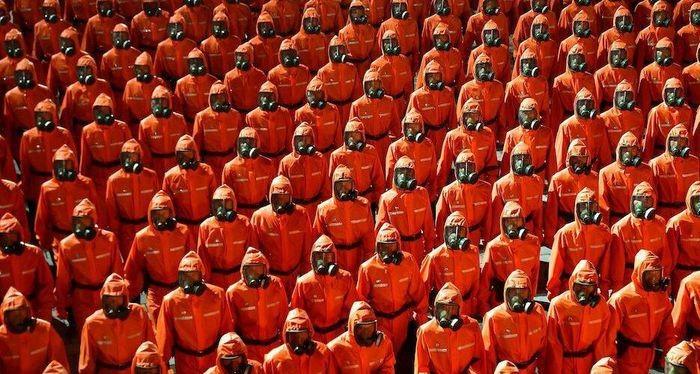 Đơn vị phòng chống dịch bệnh với bộ đồ bảo hộ màu cam và mặt nạ phòng độc trong lễ duyệt binh. (Nguồn: KCNA)