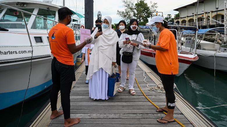 Hành khách quét một ứng dụng để theo dõi tình trạng sức khỏe trước khi lên du thuyền ở Langkawi, Malaysia, ngày 17/9.