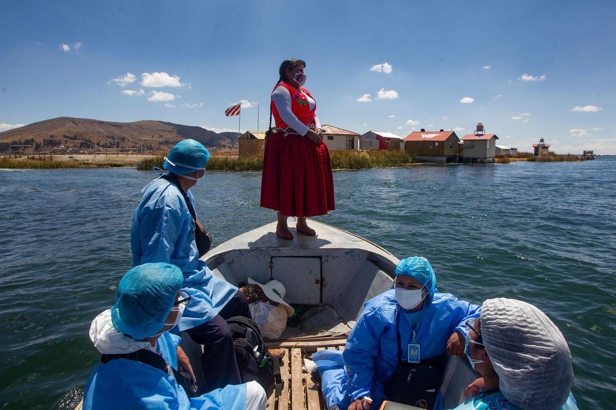 Các nhân viên y tế Peru cùng bà Rita Subana (ở giữa), cựu Thị trưởng một hòn đảo ở Uros, tham gia chương trình tiêm chủng cho những người dễ bị tổn thương chưa được tiêm vaccine Covid-19 tại các đảo nổi của Uros, thuộc khu vực hồ Titicaca, Peru, ngày 12/9