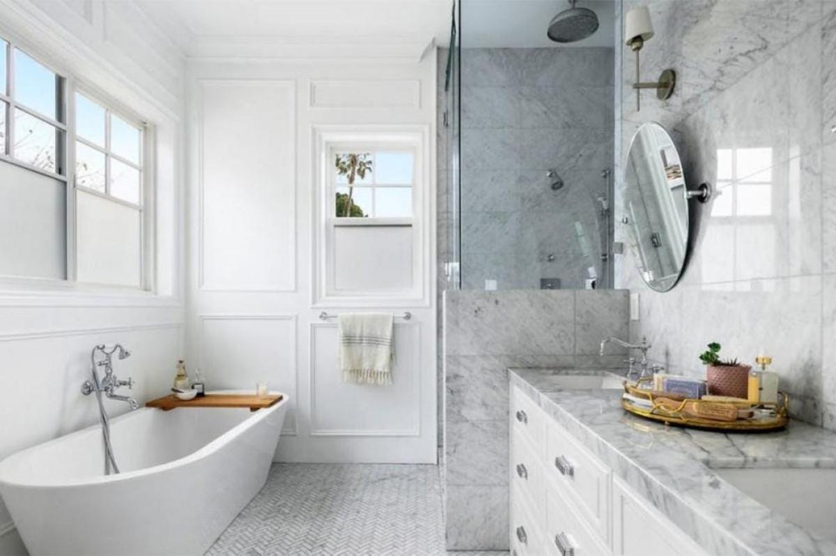 Phòng tắm được phủ bằng đá cẩm thạch Carrara và tủ màu trắng mang đến sự rung cảm hiện đại cho căn nhà.